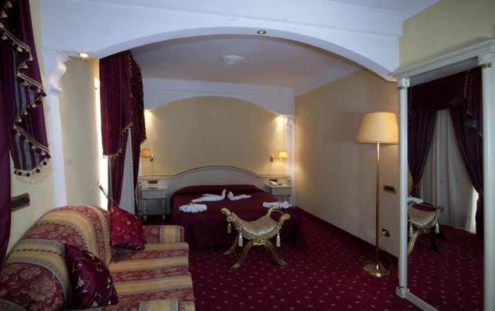 Camera matrimoniale rossa con divanetti